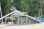 Olympus SludgePUG Pugmill system by PavementGroup.com shown set up with sludge bin, incline bin, pugmill and silo